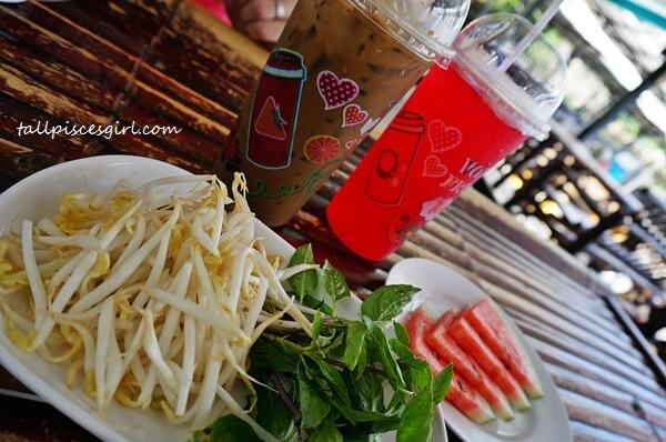 Our drinks, raw bean sprouts, leaves and complimentary watermelons