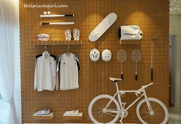 The clever use of wall space to display exercise and sports equipment is space-saving; signifies the importance of sports in the lives of the residents