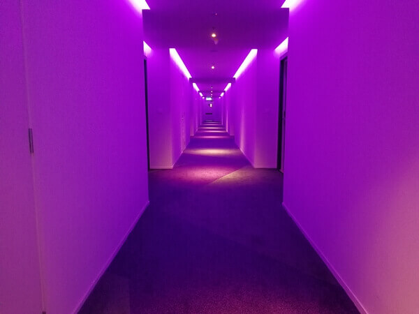 A chic trick with the corridor lighting illuminates the space in a wash of coloured light.