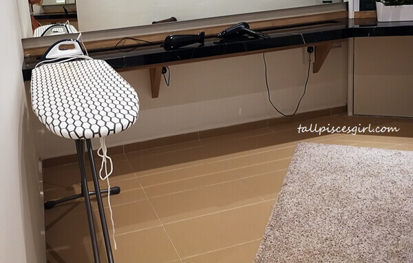 Iron and ironing board is in a separate room next to the shower area