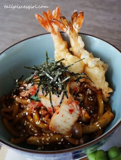 Udon wok fried with Kimchi, fresh vegetables, seaweed and sesame