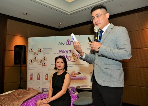 Edward Yong demonstrating the functions of Amlife electric potential thermotherapy mattress